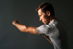 Side view of young handsome man making punches. Low key photography. Royalty Free Stock Photo