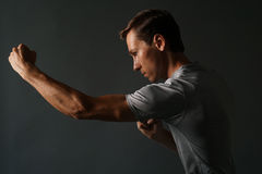 Side view of young handsome man making punches. Low key photography. Royalty Free Stock Photos