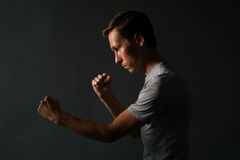 Side view of young handsome man making punches. Low key photography. Stock Images