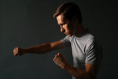 Side view of young handsome man making punches. Low key photography. Stock Image