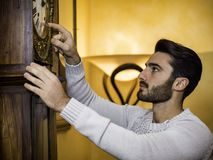 Young man setting clock stock photography