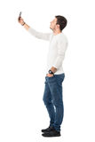 Side view of young handsome man wearing light gray shirt taking selfie with mobile phone Stock Images