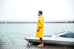 Side view of a young handsome sailor in yellow cloak. Standing at the pier Royalty Free Stock Images