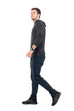 Side view of young handsome sporty man in sweatshirt and sweat pants walking looking up Royalty Free Stock Photography