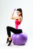 Side view of a young happy sport woman sitting on fitball with dumbells Royalty Free Stock Photography