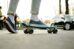 Penny skateboard commute hipster transport solutions. Side view of the young hepcat in blue jeans and canvas skate shoes crossing the road with blue plastic Stock Photography