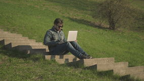 Side View of Young Hipster Man In Sunglasses Sitting On The Stairs Using Laptop. Side View of Young Hipster Man In Sunglasses Sitting On The Stairs In Park Using stock video