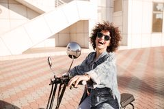 Side view of young joyful curly girl in sunglasses posing Royalty Free Stock Images