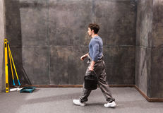 Side view of young laborer walking with paint bucket indoors. Renovation concept Stock Photos