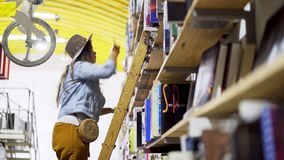 Woman on ladder searching book in library. Side view of young lady on ladder choosing volume in bookstore with decorative bicycle hanging under roof in Lisbon stock video footage