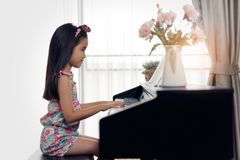 Side view of young little Asian cute girl playing electronic piano at home. stock photography