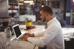 Side view of young male owner using laptop at counter Royalty Free Stock Photo