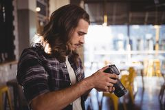 Side view of young male photographer holding DSLR camera Royalty Free Stock Photography