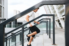 Side view of a young male runner running upstairs. At the stadium Stock Photography