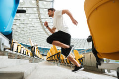 Side view of a young male runner running upstairs. At the stadium Royalty Free Stock Image