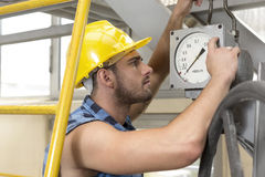 Side view of young male worker checking pressure gauge in industry Stock Images