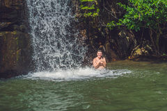 Side view of young man with arms standing against waterfall Royalty Free Stock Image