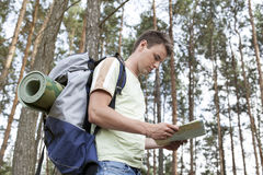Side view of young man with backpack reading map in woods Stock Images