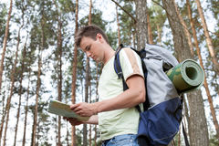 Side view of young man with backpack reading map in woods Royalty Free Stock Photo