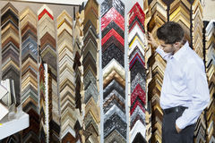 Side view of a young man browsing at a frame store with hands in pockets Stock Photography