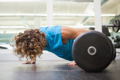 Side view of young man doing push ups in gym Stock Photography