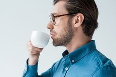 Side view of young man drinking coffee from cup. Isolated on white stock images