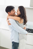 Side view of a young man embracing woman in kitchen Royalty Free Stock Image