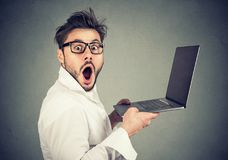 Astonished young man holding laptop royalty free stock photography