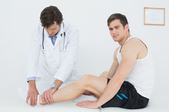 Side view of a young man getting his ankle examined Stock Images