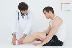 Side view of a young man getting his ankle examined Royalty Free Stock Photos