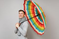 Side view of young man in gray sweater, scarf hold colorful umbrella looking up on grey background. Healthy royalty free stock photo