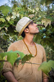 Side view of young man in hat looking at vine leaves Royalty Free Stock Photo