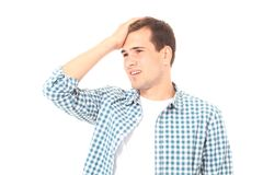Side view of young man with headache touching forehead on white background. Student failed the exam. Copy space. Side view of young man with headache touching Stock Photo