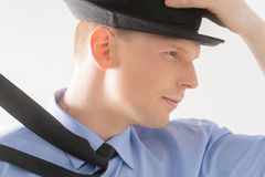 Side view of young man holding hat. Royalty Free Stock Photos