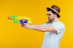 side view of young man holding water gun and looking away royalty free stock photo