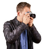 Side view from a young man with a leather jacket holding a vintage camera and pointing at the camera - . Royalty Free Stock Image
