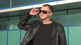 Side view of young man in leather jacket and sunglasses standing outdoor.  stock video footage