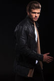 Side view of a young man in leather jacket is walking Royalty Free Stock Photo
