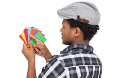 Side view of a young man looking at colorful papers Stock Image
