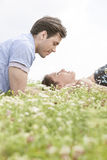 Side view of young man looking at woman sleeping on grass against sky Stock Images