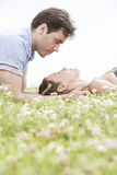 Side view of young man looking at woman sleeping on grass Royalty Free Stock Image