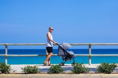 Side view of young man pushing baby stroller on the beach royalty free stock photos