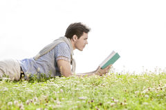 Side view of young man reading book while lying on grass against clear sky Stock Photo