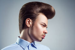 Side view of young man with retro classic pompadour hairstyle. Studio shot stock photography