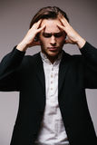 Side view of young man in shirt touching his head and keeping eyes closed Royalty Free Stock Photography