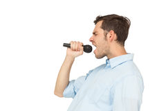 Side view of a young man singing into microphone stock photography