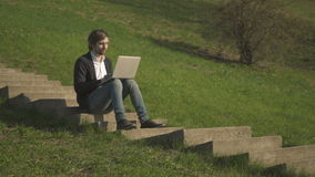 Side View of Young Man Sitting On The Stairs In Park Using Laptop. Outdoors, 4K stock footage