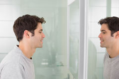 Side view of a young man smiling at self in bathroom mirror Royalty Free Stock Photo