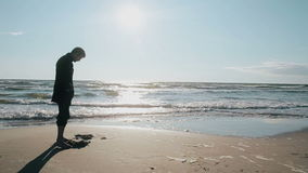 Side view of a young man standing barefoot on the beach on a lovely sunny day digging a hole in the sand with his toes. A side view of a young man in a black stock footage