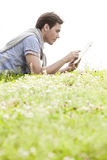 Side view of young man using digital tablet while lying on grass against clear sky Stock Photos